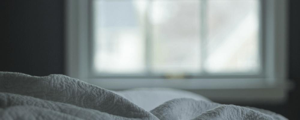 Weiße Bettwäsche auf einem Bett vor dem Fenster durch das viel Licht in das Zimmer eindringt.